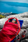 picture of sleeping bag  - Young woman lying in red sleeping bag on the rocky mountain - JPG