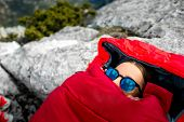 foto of sleeping bag  - Young woman lying in red sleeping bag on the rocky mountain - JPG