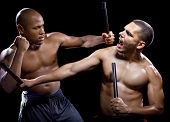 foto of filipino  - two muscular martial artists sparring on a black background - JPG