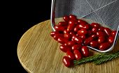 image of plum tomato  - Stainless steel basket filled with plum tomatoes with rosemary sprigs on a bamboo cutting board isolated on black