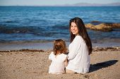 stock photo of babysitter  - Mother and daughter relaxing and sitting together at the beach - JPG