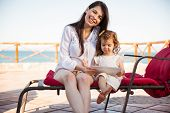 stock photo of babysitter  - Portrait of a beautiful Hispanic mother and her daughter playing games on a tablet computer while relaxing at the beach - JPG
