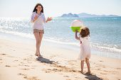 foto of sunny beach  - Cute little girl throwing a beach ball at her mom and having some fun on a sunny day - JPG