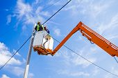 pic of pole  - Technician works in a bucket high up on a power pole - JPG