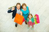 picture of mall  - Top view of cheerful family holding shopping bags and smiling at camera while standing in shopping mall - JPG