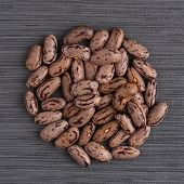 stock photo of pinto bean  - Top view of circle of pinto beans against grey vinyl background - JPG