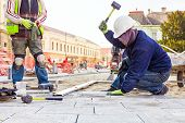 stock photo of paving  - Workers stack paving block on city street - JPG
