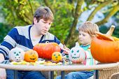stock photo of jack-o-lantern  - Little kid boy and his father making traditional jack - JPG