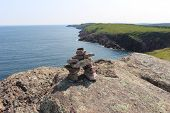 image of spears  - Welcoming Inukshuk in the foreground and Cape Spear  - JPG