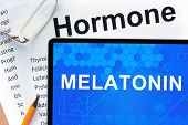 picture of hormone  - Papers with hormones list and tablet  with words  melatonin - JPG