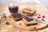 picture of dry fruit  - Fresh baked homemade healthy bread with blackcurrant jam -  marmalade with fresh organic fruits from garden. In rustic decoration,dried roses, silver spoon and knife, fruit jam on toasted breadon wooden table background. 