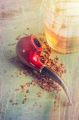 foto of tobacco-pipe  - Tobacco pipe on rustic warn green wood surface with spilled natural tobacco and a glass of whisky on the rocks - JPG