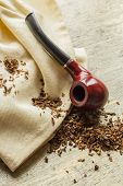 stock photo of tobacco-pipe  - Tobacco pipe on rustic warn wood surface with spilled natural tobacco - JPG