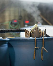 foto of respirator  - A respirator chemical safety equipment sits on a 55 gallon drum in a chemical plant. Gasses emit from containers in the background. Corrosive industrial environment. ** Note: Visible grain at 100%, best at smaller sizes - JPG