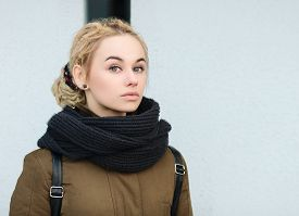 image of sarcastic  - Outdoors portrait of sarcastic young beautiful blonde hipster woman in olive parka with a dreadlocks bun hairstyle - JPG