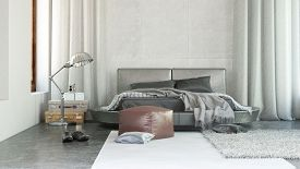 pic of ottoman  - Stylish modern bedroom interior with grey decor and rugs thrown over a double bed with ottoman and long drapes on either side - JPG