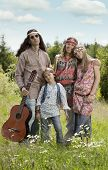 foto of hippy  - Portrait of hippie family standing in the field on a sunny summer day - JPG