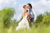 pic of sparkling wine  - Wedding bride and groom toasting with sparkling wine outside on field - JPG