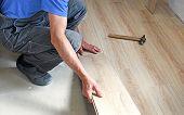 pic of laminate  - male carpenter puts the laminate in the room - JPG