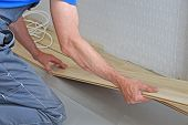 stock photo of laminate  - hands of a carpenter install laminate in the room - JPG