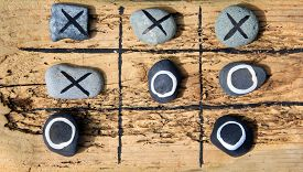 stock photo of tic  - Tic tac toe game made from drift wood and rocks for outdoor garden play - JPG