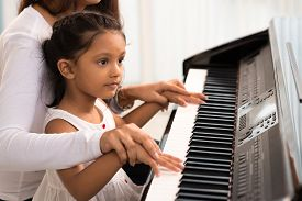 foto of modifier  - Woman helping her daughter to play the piano body and buttons of the piano were digitally modified - JPG