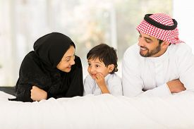 picture of muslim  - happy young muslim family of three lying on bed at home - JPG