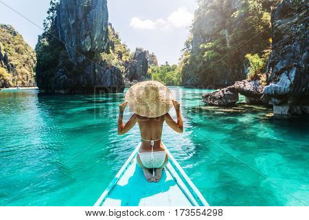 poster of Back view of the young woman in straw hat relaxing on the boat and looking forward into lagoon. Trav