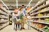 sale, consumerism and people concept - happy family with child and shopping cart buying food at groc poster