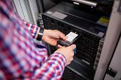 Technician inserting a hard disk drive into a blade server in server room poster