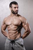 Brutal Strong Bodybuilder Man Posing In Studio On Grey Background. poster
