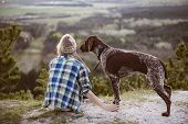 Woman and her dog posing outdoor. Girl loving and touching her dog paws and watching landscape. poster