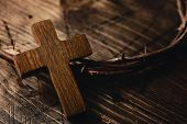 closeup of a small wooden cross and a depiction of the crown of thorns of Jesus Christ on a wooden s poster