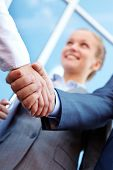 Photo of successful associates handshaking after striking deal outdoors at meeting
