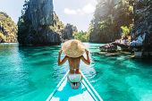 Back view of the young woman in straw hat relaxing on the boat and looking forward into lagoon. Trav poster