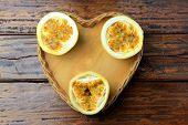 Yellow Passion Fruit And Passion Fruit Cut In Half In Heart-shaped Basket On Wooden Table. poster
