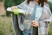 Hands Of Girl With Thermos Pours Hot Tea Into Mug On Meadow On Background Of Trees At Misty Morning. poster