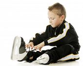 A cute preschooler loosening the laces on his hockey skates.  On a white background.