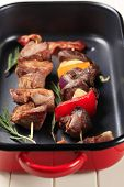 Shish kebabs and rashers of bacon in a roasting pan