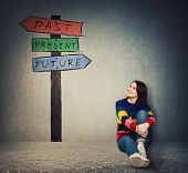 Young Woman Sitting On The Floor Looking At A Signpost With Arrows That Shows Past, Present And Futu poster