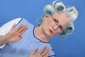 grandmother with hair curlers against blue background