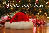 Christmas Images. Santa Hat. Santa Claus Hat under a Christmas Tree. Text overlay reads Santa was he poster