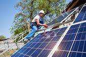 Young Technician In Protective Helmet On Tall Metal Platform Installing Heavy Solar Photo Voltaic Pa poster