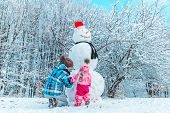 Mother With Daughter Playing Outside In Winter Time. Making Snowman Concept poster