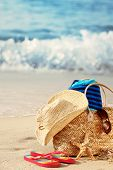foto of summer beach  - Closeup of summer beach bag with items on sandy beach - JPG