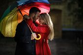 Beautiful Couple Hugging Outside And Standing Under Colorful Umbrella. Love Story Concept. poster