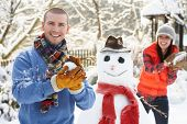 pic of snowball-fight  - Young Couple Having Snowball Fight In Garden - JPG
