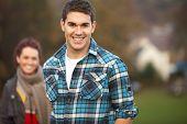 Teenage Boy Outside With Girlfriend In Background