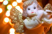 Figurine Of Little Angel With Golden Shiny Wings And Halo That Plays Flute On Shining Background Of  poster