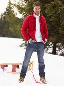 stock photo of toboggan  - Young Man With Sled In Alpine Snow Scene - JPG